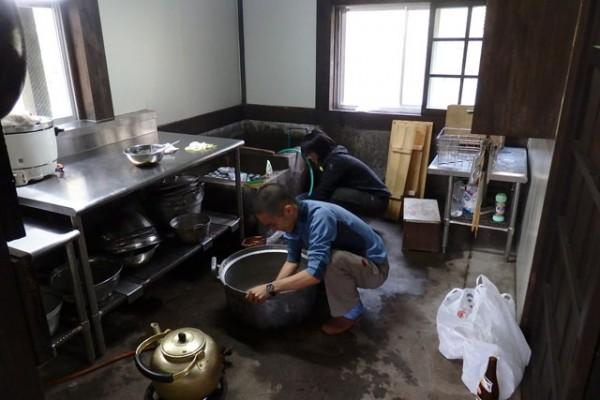 大鍋に湯を張り、食器を洗う